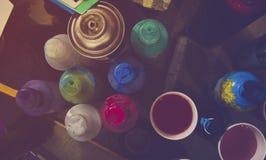 Schreibtischwerkstatttabelle des Graffitikünstlers, der eine Farbe, Spraydosen, Aquarelle und Skizzen auf dem Tisch skizziert Lizenzfreies Stockfoto
