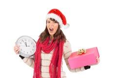 Schreien des Brunette, der eine Uhr und ein Geschenk hält Stockfotografie