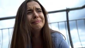 Schreiende Frau, die auf Straße, Auseinanderbrechen oder Verlust der nahen Person, Geistesstörung sitzt stockfotografie