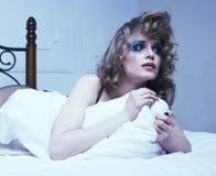 Schreiende Frau, die in das Bett niedergedrückt, wirkliches blondes legt Lizenzfreies Stockfoto