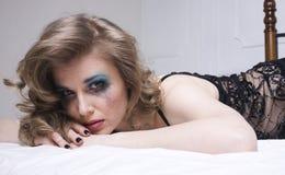 Schreiende Frau, die in das Bett niedergedrückt, wirkliches blondes legt Stockfotos