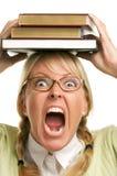 Schreiende Frau unter Stapel Büchern auf Kopf Stockfotografie