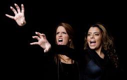 Schreiende junge Frauen, die Handgeste zeigen Stockfotos