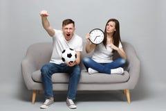 Schreiende Paarfrauen-Mannfußballfane jubeln oben Stützlieblingsteam mit Fußball zu und halten die runde Uhr und pressen zusammen lizenzfreies stockfoto