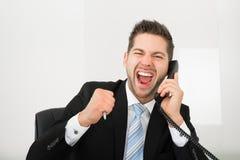 Schreiender Geschäftsmann bei der Anwendung des Überlandleitungstelefons im Büro Lizenzfreies Stockfoto