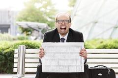 Schreiender Geschäftsmann mit Zeitung in seinen Händen Lizenzfreie Stockfotografie