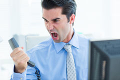 Schreiender Geschäftsmann, wie er heraus Telefon im Büro hält Stockfotografie