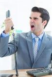 Schreiender Geschäftsmann, wie er heraus Telefon im Büro hält Stockfoto