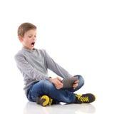Schreiender Junge, der eine Tablette verwendet. Lizenzfreie Stockfotos