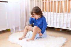 Schreiender kleiner Junge, der auf Töpfchen sitzt Stockbilder
