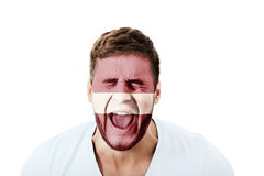 Schreiender Mann mit Lettland-Flagge auf Gesicht stockfotografie