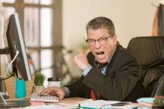 Schreiender Mann an seinem Schreibtisch lizenzfreie stockbilder