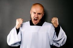 Schreiender umgekippter katholischer Priester im weißen Chorhemd stockbild