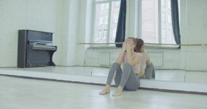 Schreiender weiblicher Tänzer, der auf Spiegel im Studio sich lehnt stock footage