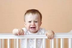 Schreiendes Baby im weißen Bett Stockbilder