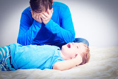Schreiendes Kind, müder Vater Lizenzfreie Stockfotografie