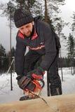 Schreiner schneidet einen Klotzbaumstamm mit Kettensäge Lizenzfreies Stockfoto
