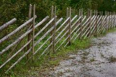 Schräg liegender Zaun hergestellt von den Pfosten in den ländlichen Gebieten Stockbild