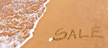 Schriftlicher Verkauf gezeichnet auf den Sand Stockfotografie