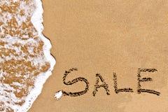Schriftlicher Verkauf gezeichnet auf den Sand Stockbild