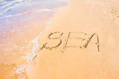 Schriftliches Meer auf Sand an der Küste, Hintergrund Lizenzfreie Stockfotos