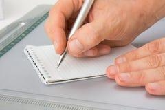 Schrijf met een pen in een notitieboekje royalty-vrije stock foto