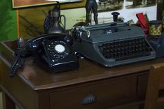 Schrijfmachines en oude telefoons op de houten lijst royalty-vrije stock afbeeldingen