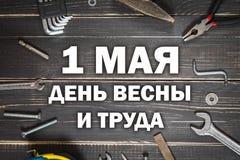 Schrijnwerkerijhulpmiddelen op een donkere houten lijst Plaats voor de tekst Tekst in Rus: 1 mei, Dag van de Lente en Arbeid stock foto