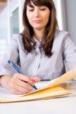 Schrijven het bedrijfs van de Vrouw nota's bij bureau royalty-vrije stock afbeeldingen