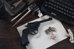 Schrijvend een verhaal van de misdaadfictie - oud retro uitstekend schrijfmachine en revolverkanon met munitie, boeken, leeg docu royalty-vrije stock foto's
