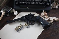 Schrijvend een verhaal van de misdaadfictie - oud retro uitstekend schrijfmachine en revolverkanon met munitie, boeken, leeg docu stock fotografie