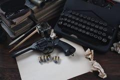 Schrijvend een verhaal van de misdaadfictie - oud retro uitstekend schrijfmachine en revolverkanon met munitie, boeken, leeg docu royalty-vrije stock afbeelding