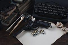 Schrijvend een verhaal van de misdaadfictie - oud retro uitstekend schrijfmachine en revolverkanon met munitie, boeken, leeg docu royalty-vrije stock afbeeldingen