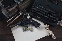 Schrijvend een verhaal van de misdaadfictie - oud retro uitstekend schrijfmachine en revolverkanon met munitie, boeken, leeg docu royalty-vrije stock fotografie