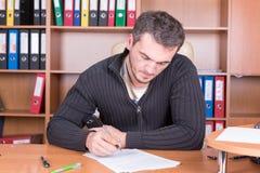 Schrijvende ongeschoren mens in bureau Stock Afbeelding