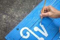 Schrijvende tekensraad met een borstel van waterverf op de achtergrond van de cementvloer Het schilderen op houten raad in Thaise stock foto's