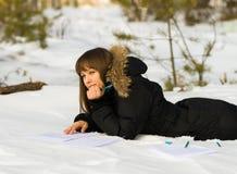 Schrijvende vrouw in de winterbos Stock Foto