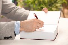 Schrijver die autograph in boek ondertekenen bij lijst stock afbeeldingen