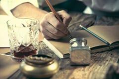 Schrijver op het werk De handen van jonge schrijverszitting bij de lijst en het schrijven van iets in zijn sketchpad stock fotografie