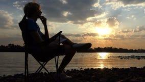 Schrijver Sitting op de Stoel bij Zonsondergang op de Schoonheid Riverbank stock video