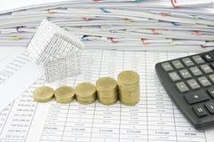 Schritt der Goldmünze nahe Haus mit Taschenrechner Lizenzfreies Stockfoto