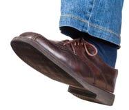 Schritt des männlichen linken Beines in den Jeans und im braunen Schuh Stockbilder