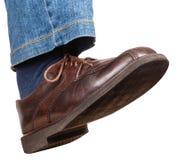 Schritt des männlichen rechten Beines in den Jeans und im braunen Schuh Stockfotos