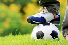 Schritt des menschlichen Fußes auf Fußball Lizenzfreies Stockfoto