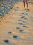 Schritt von weiblichen Beinen im Sand auf dem Strand bei Sonnenaufgang Lizenzfreies Stockbild