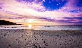Schrittbahnen im Sand auf Strand mit Sonnenaufgang oder Sonnenuntergang Lizenzfreie Stockbilder