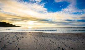 Schrittbahnen im Sand auf Strand mit Sonnenaufgang oder Sonnenuntergang Stockfotos