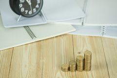 Schritte des Münzenstapels mit Weinlesewecker und Stift, Notizbuch Lizenzfreie Stockfotografie