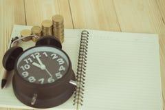 Schritte des Münzenstapels mit Weinlesewecker und Stift, Notizbuch Lizenzfreies Stockfoto
