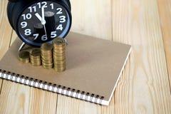 Schritte des Münzenstapels mit Weinlesewecker und Stift, Notizbuch Lizenzfreie Stockbilder